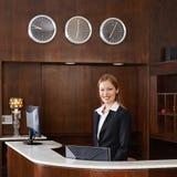 Receptionnist achter teller bij hotel stock afbeelding