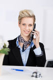 Receptionnist Using Cordless Phone bij Bureau Royalty-vrije Stock Foto