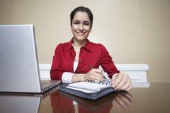 Receptionnist Writing In Diary in Bureau royalty-vrije stock foto's