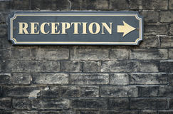 Receptions arrow sign on brick wall. Reception sign on black brick wall Stock Images
