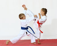 Receptions of self-defence protecting from an attack a girl beats a leg a boy beats a hand. Professionally good sport karate kids stock photo