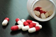 Receptläkarbehandlingpreventivpillerar i öppnad plast- medicinflaska Royaltyfri Foto