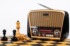 Receptor de radio en estilo retro con los pedazos de ajedrez en el tablero de ajedrez y el fondo blanco Imagen de archivo