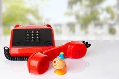 Receptor de telefone vermelho do vintage com cabo preto na tabela branca mim imagem de stock