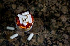 Receptpreventivpillerflaska med vita kapslar på marmorcountertop Arkivbild