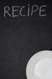 Recepttiteln är skriftlig i krita på en svart tavla och tömmer plattan Arkivfoton