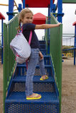 Recess time. Young school girl on playground equipment Royalty Free Stock Photo