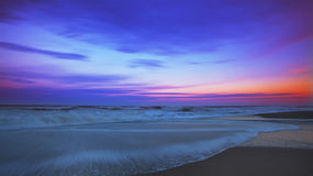 Recessing a maré e o moonrise sobre o oceano arenoso encalhe Imagem de Stock