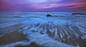 Recessing Tide And Moonrise Over Sandy Ocean Beach Stock Photo