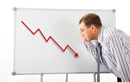 Recession. Image of serious man inclining to whiteboard and looking at recession graph on it royalty free stock photography
