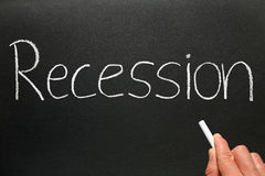 Recession on blackboard. Recession written on chalk board and hand holding chalk stock image