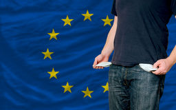 Recession impact on young man  in europe. Poor man showing empty pockets in front of europe flag Royalty Free Stock Photos