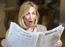 Recession in the newspaper. Mature woman reading the financial news royalty free stock photos