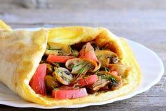 Receta de la tortilla de las setas y de los tomates Tortilla casera rellena con las setas fritas, los tomates frescos y los verde Imagen de archivo