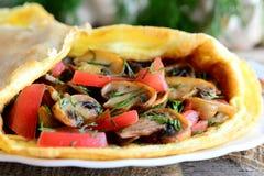 Receta de la tortilla de las setas y de los tomates Tortilla casera rellena con las setas fritas, los tomates frescos y los verde Foto de archivo