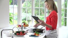 Receta de siguiente de la mujer en la tableta de Digitaces mientras que cocina