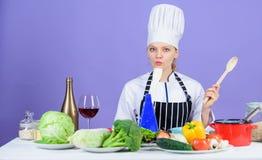 Recetas gastrónomas del plato principal El cocinar es su afición Cocinar el alimento sano Muchacha en sombrero y delantal El coci imágenes de archivo libres de regalías