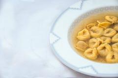 Recette d'hiver : bouillon avec le tortellini italien images libres de droits