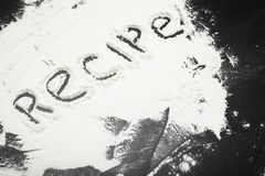 Recette - le mot écrit avec un doigt sur la farine, fond noir image libre de droits