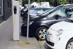 Recharge. Electric Car in Free Charging Station. Environmentally Friendly Transport Stock Photos