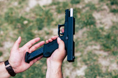Recharge the gun in your hand. Training on shooting Royalty Free Stock Photo