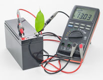 Rechargeable battery with connected measuring instrument and green leaf. Royalty Free Stock Images