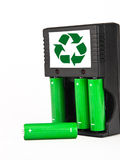 Rechargeable green batteries with black charger on. Eko green batteries with charger Royalty Free Stock Photography