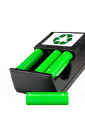 Rechargeable green batteries with black charger on. Eko green batteries with charger Royalty Free Stock Image