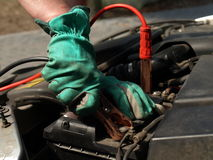 Recharging car battery. Man hands in gloves recharging battery in car Stock Photos