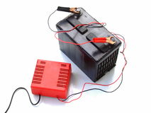 Recharging a Car Battery. A 12 volt automotive battery connected up to a mains-powered charger - isolated over pure white Royalty Free Stock Photo