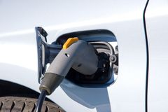 Recharging an electric car. Recharging a silver electric car Royalty Free Stock Images