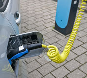 Recharging an electric car. Close-up image of an electric car hooked up to an electricity charging station Royalty Free Stock Photo