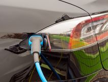 Charging an electric car. Recharging of an an electric car with a plug and cable royalty free stock photography