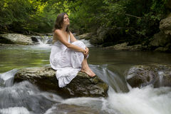 Recharging with Nature. Beautiful young girl enjoying the purifying herself in the clear water of a mountain stream Stock Image