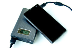 Recharging smart phone from Metalic powerbank. Digital display on white background Stock Photography
