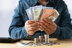 rechenkundiges Geld der Geschäftsfrau für die Rettung, Finanzerklären conc Stockfotografie