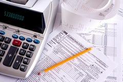 Rechenmaschine mit Steuerformularen Stockbild