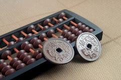 Rechenmaschine und chinesische Münzen stockfoto