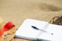 Recherche de l'inspiration sur la plage : mer, sable, bloc-notes et stylo, l'espace de copie images stock