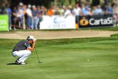 Recherche inconnue de concentré de joueur de golf de Turin Italie que la ligne s'est accroupie sur le vert photographie stock