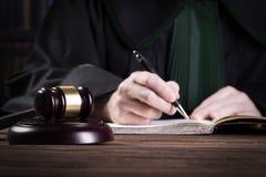 recherche Le marteau du juge en bois et les livres de loi avec le traitement des lois, des questions juridiques, ou des cas images stock