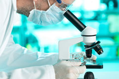 Recherchez le scientifique travaillant avec le plat de spécimen sur l'esprit de microscope image libre de droits