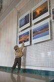 RECHITSA Vitryssland - April 20, 2016: En pojkelätthet uppför fotobilder på en utställning i den kulturella mitten av svart guld Arkivbild