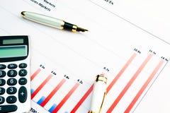 Rechner auf einem Finanzdiagramm Stockbilder