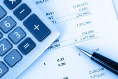 Rechner auf Finanzreport mit blauem Hintergrund Lizenzfreies Stockbild