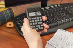 Rechner in der Hand des Schülers über dem Desktop Lizenzfreies Stockbild