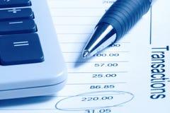Rechner und Feder auf Finanzberichten Stockbilder