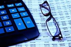 Rechner und Gläser oben auf Finanzpapier Stockfotos