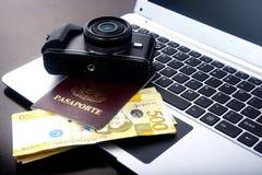 Rechnungen der Kamera, des Passes und des philippinischen Pesos auf einer Laptop-Computer Stockfotografie