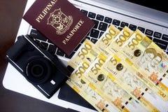 Rechnungen der Kamera, des Passes und des philippinischen Pesos auf einer Laptop-Computer Stockbild